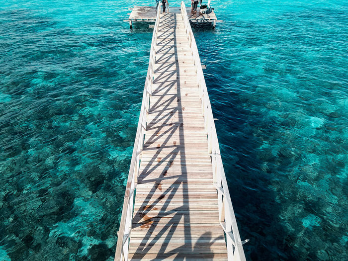 Aerial top view of wooden pier bridge, walkway to the sea in cleared and clean seawater