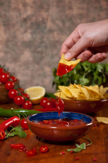 Cropped hand dipping nachos in sauce on table