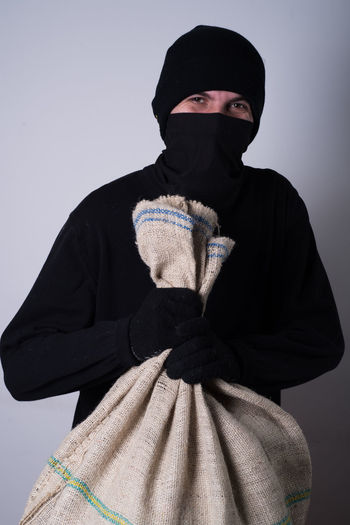 Portrait of man in costume holding sack while standing against wall