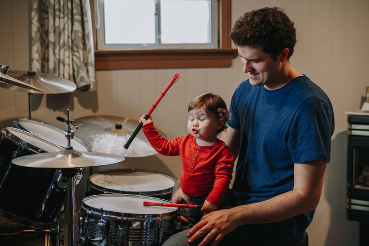 Father looking at cute baby son making face while playing drums