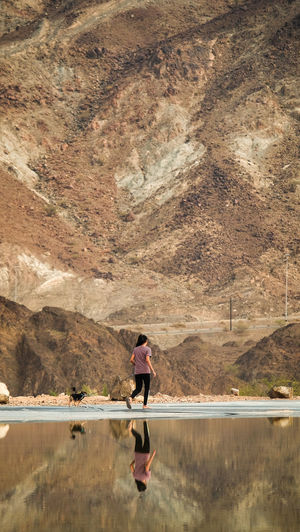 A young female teenager walking with a small dog in the mountains beside a clear mirror lake in Hatta, United Arab Emirates One Person Water Full Length Day Nature Mountain Outdoors Adult Scenics - Nature Women Lake Lifestyles Beauty In Nature Real People Young Adult Side View Leisure Activity Tranquility Portrait Walking Dog Reflections In The Water Early Morning Hiking Camping