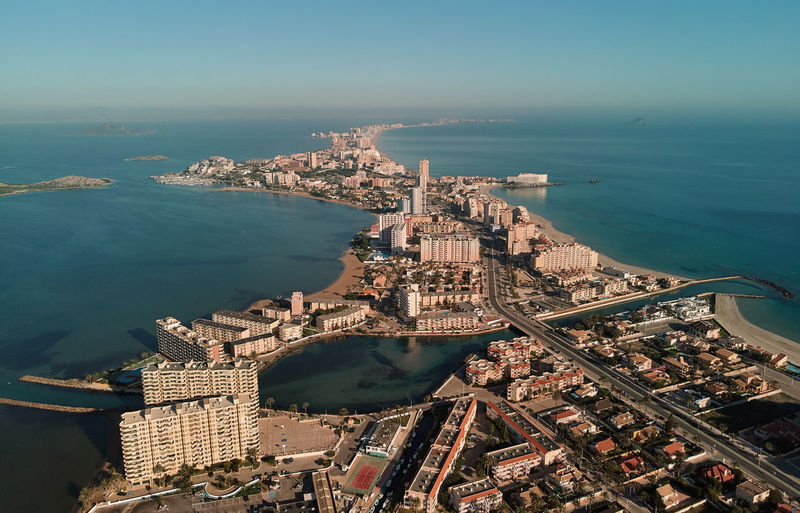 Aerial view of city by sea against sky