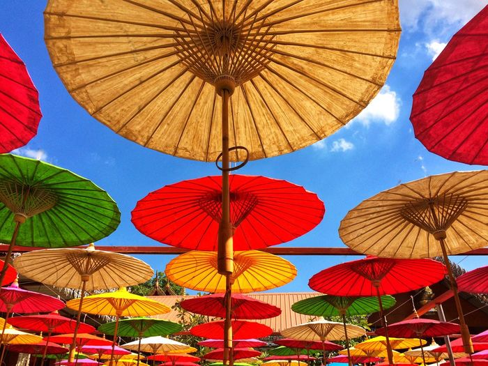 Colorful paper umbrellas floating in the sky. Sun Rain UV  Umbrella Protection Parasol Security Low Angle View Multi Colored Sky Day Outdoors No People Beach Umbrella Beauty In Nature Summer Safety Pattern