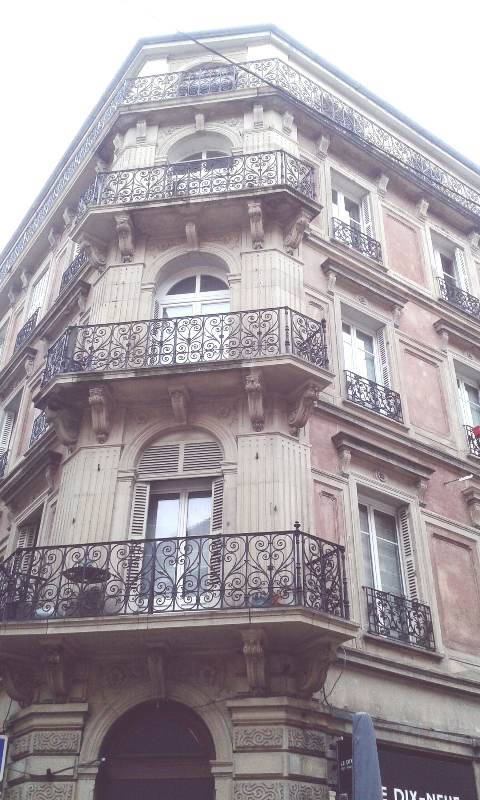 architecture, building exterior, built structure, low angle view, window, arch, building, facade, sky, day, outdoors, no people, city, residential building, clear sky, old, history, residential structure, balcony, architectural feature