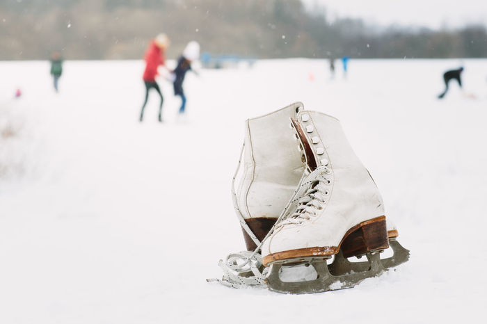 A pair of female ice skates lying on the snow with skaters in the background. A pair of white retro ice skates on the snow. Natural Pond Winter Wintertime Close-up Cold Temperature Day Frozen Ice Ice Rink Ice Skate Ice Skates Ice Skating Ice-skating Incidental People Nature Outdoors Rink Snow Snowing Snowy Weather White Color Winter Winter Sport