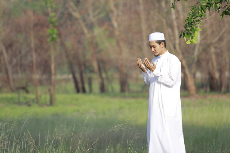 Man In Traditional Clothing Praying While Standing On Field