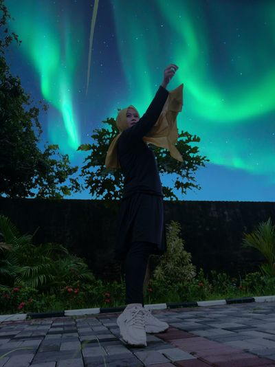 Full length of woman standing against aurora at night