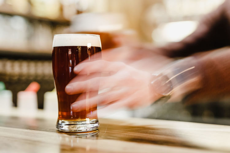 Cropped hands holding beer glass on table