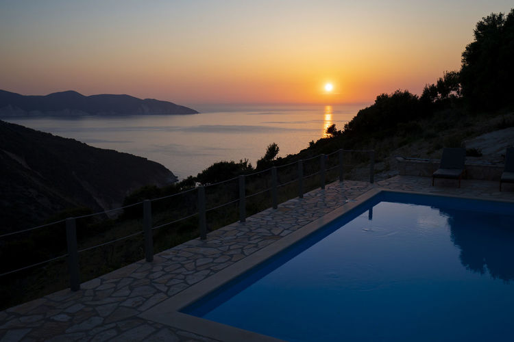 Scenic view of swimming pool by sea against sky during sunset