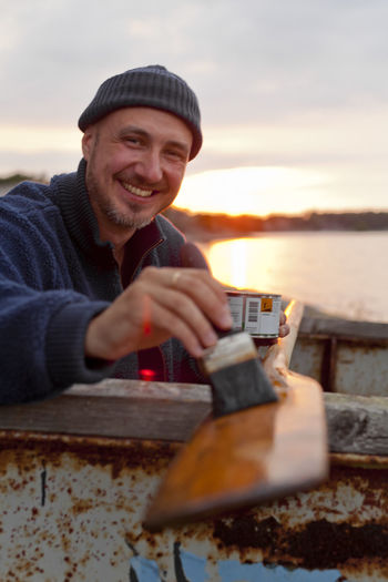 Portrait of smiling man holding ice cream against sky during sunset
