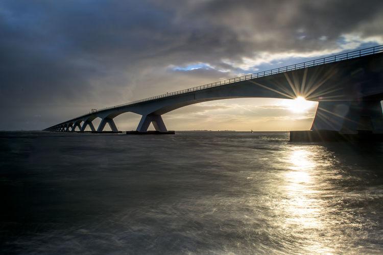 Zeeland Bridge Over River Against Cloudy Sky