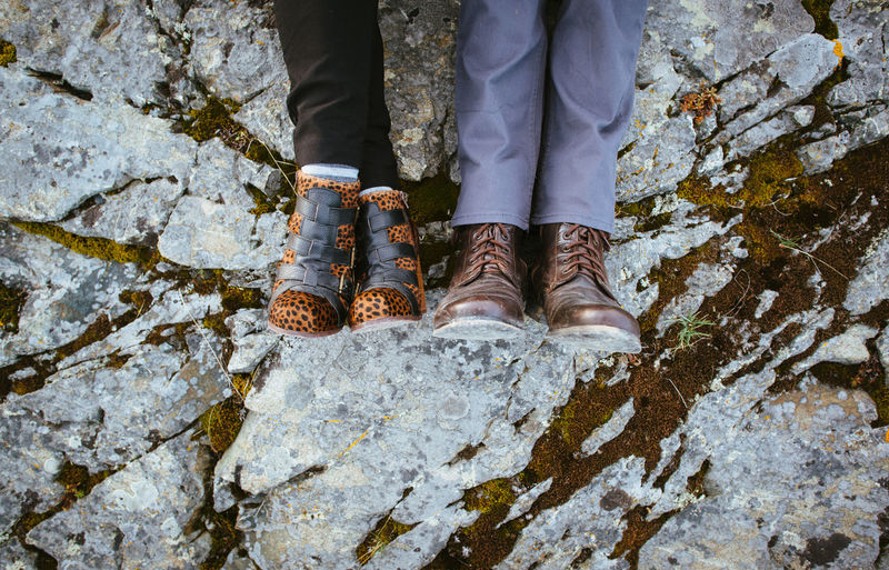 Low Section Of People Wearing Shoes Lying On Rock