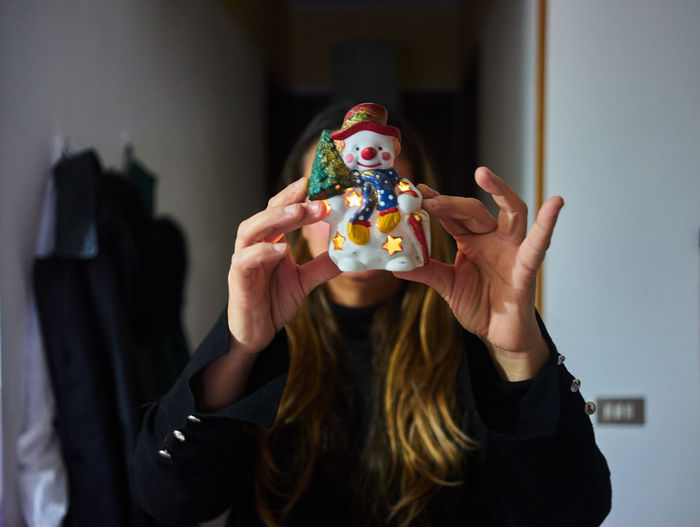 Woman Showing Snowman Figurine