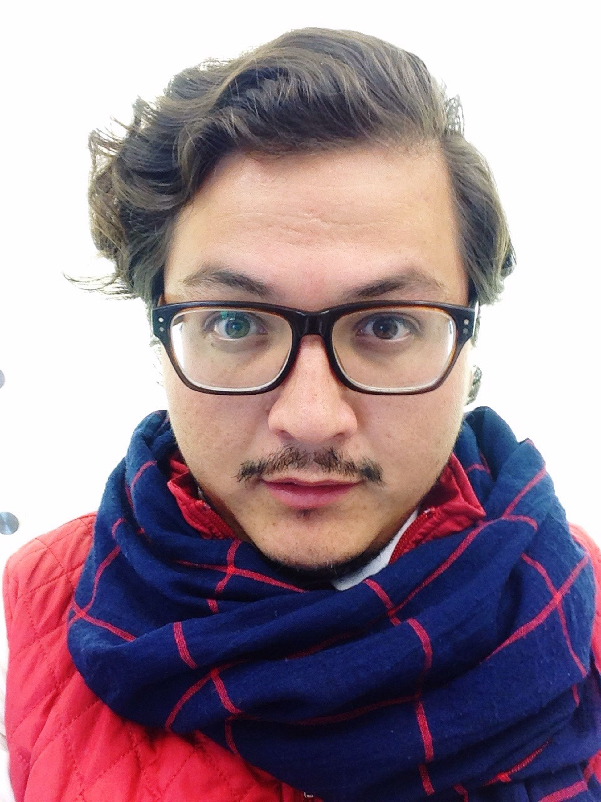 looking at camera, portrait, real people, one person, human face, facial expression, red, sweater, studio shot, eyeglasses, handsome, mature adult, young adult, front view, scarf, lifestyles, adults only, making a face, facial hair, only men, men, close-up, senior adult, white background, warm clothing, adult, people, one man only, human body part