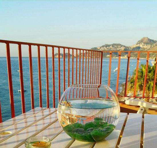 Fish bowl on table by sea against clear sky