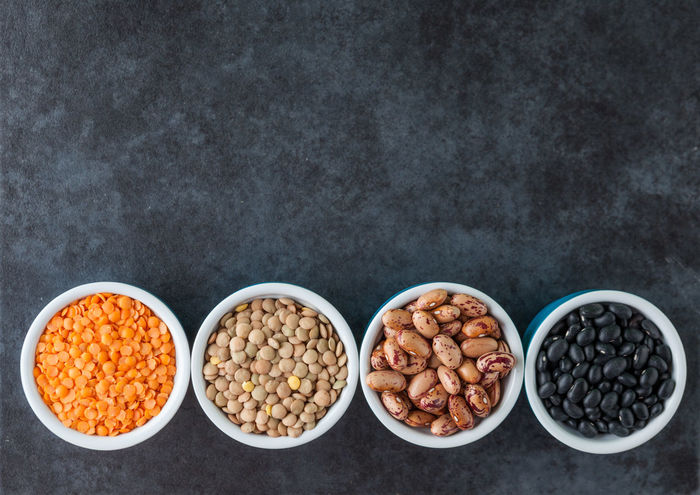 Red and brown lentils, heirloom beans, and black turtle beans on dark grungy surface. Top view with copy space. Copy Space Bowl Close-up Coffee Bean Day Food Food And Drink Freshness Grain Grains Healthy Eating Heirloom Beans Indoors  Lentils No People Nut - Food Raw Food Still Life Turtle Beans Variation