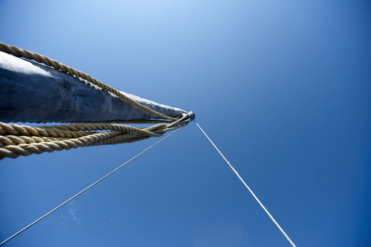 Low Angle View Of Mast Against Clear Blue Sky During Sunny Day