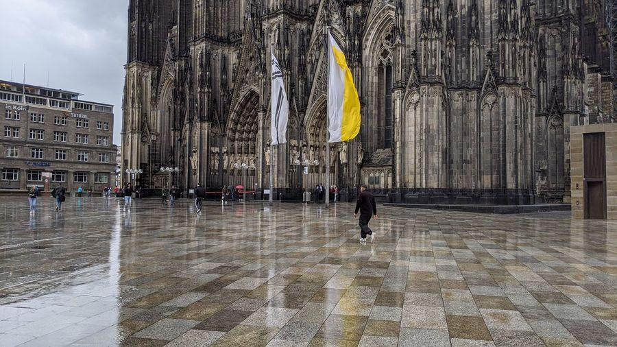 Group of people walking on wet floor in city