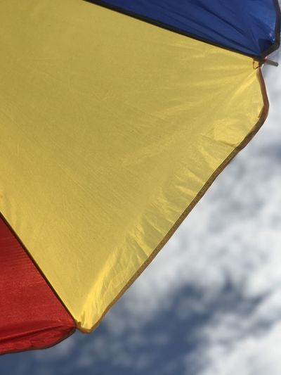Low angle view of yellow umbrella against sky