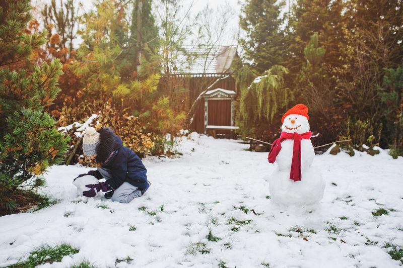 Girl Making Snowman In Backyard