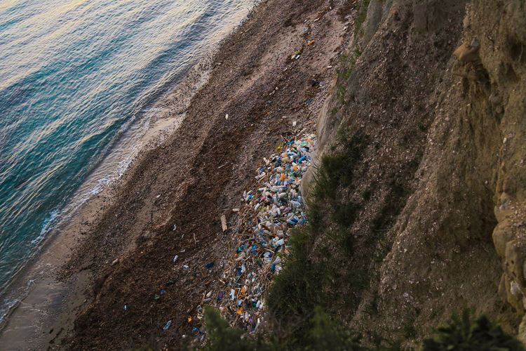 High angle view of garbage by cliff at beach during sunset