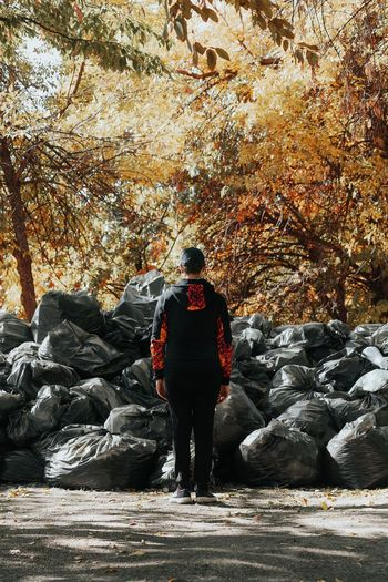 Rear View Of Man Standing Against Garbage Bags At Park During Autumn