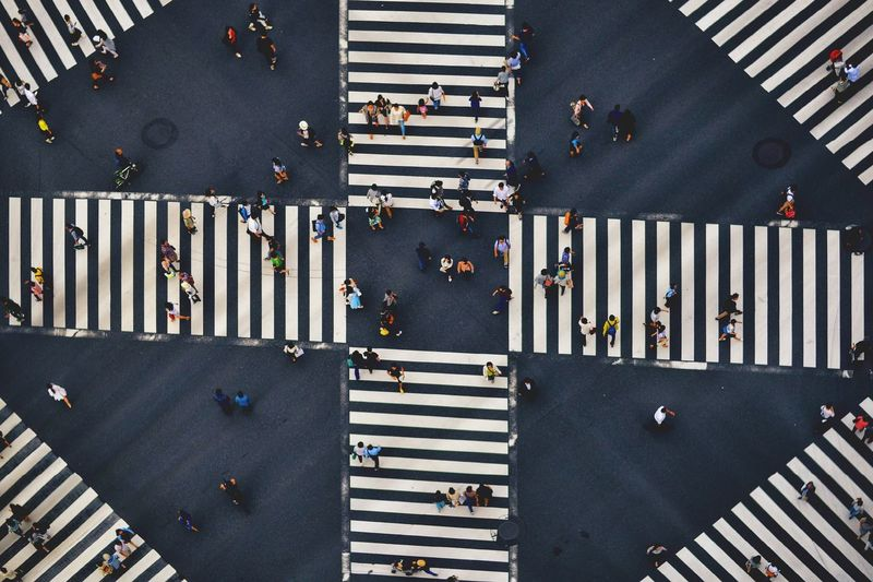 Aerial View Of People Walking On Road Intersection In City