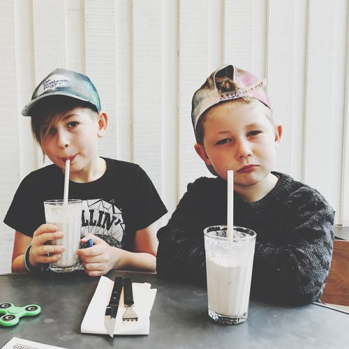 Two young boys looking to camera drinking milkshakes. Portrait Happiness Burgers Gourmet Sons Real People Dude Cool Kids Cool Boys Drink Child Childhood Drinking Two People Drinking Straw Portrait Children Only Milkshake Indoors  Lifestyles Milk Food And Drink Drinking Glass Refreshment Front View Togetherness