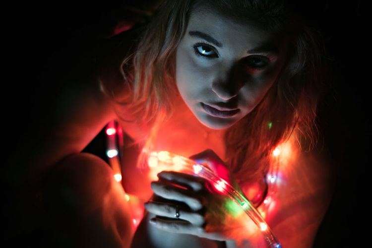Close-up portrait of young woman with led lights