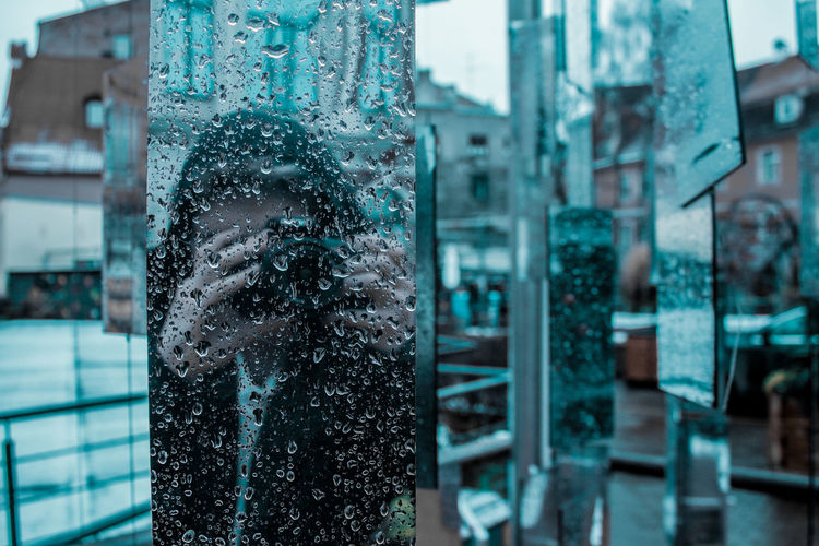 Woman photographing reflecting on wet glass