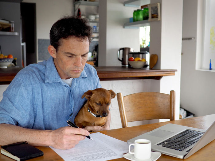 Businessman with dog doing paperwork at desk in home