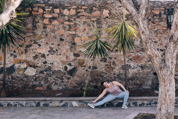 Side view of woman sitting by wall stretching
