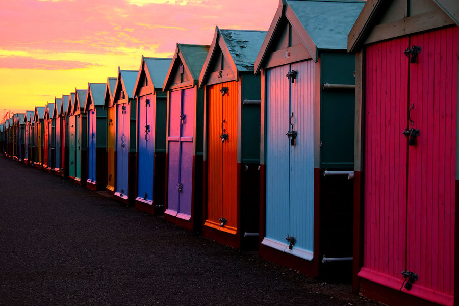 Brighton Beach Brighton And Hove Colourful Evening Light Sunset Glow Architecture Beach Huts Beach Huts And Evening Sky Brighton Promenade Brighton Uk Brightonbeach Building Exterior Built Structure Day Evening Walk Huts In A Row Multi Colored No People Outdoors Sky Sunsets