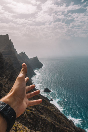 Cropped hand of man gesturing against sea