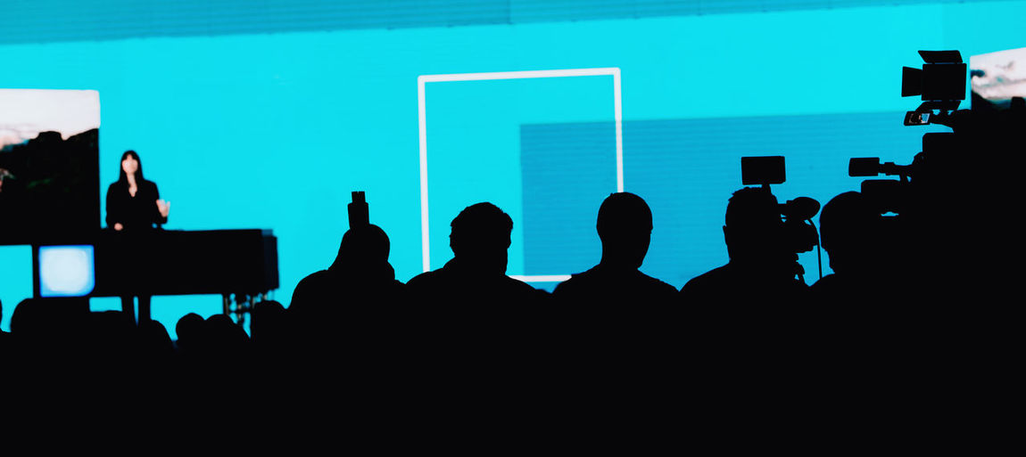 Female Speaker on the Stage at Media Press Conference Media Press Conference Silhouette Camera Speaker News Reportage Presentation Communication Public Event Technology Equipment Speech Meeting Seminar Television Politician Politics Entertainment Bussiness Jurnalist Government Stage Corporate Live Leadership Campaign Correspondent Broadcast Blue Group Of People Crowd Copy Space Projection Screen Unrecognizable Person
