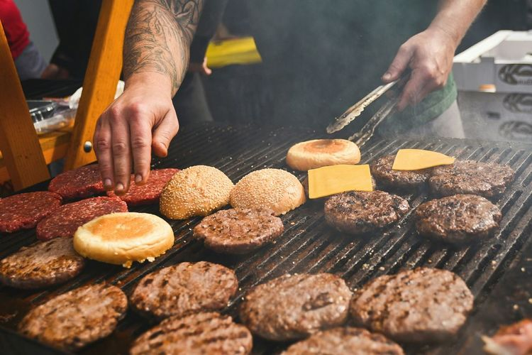 Midsection of man preparing burgers on barbecue grill
