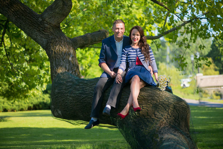 Portrait of man and woman sitting on tree trunk at park