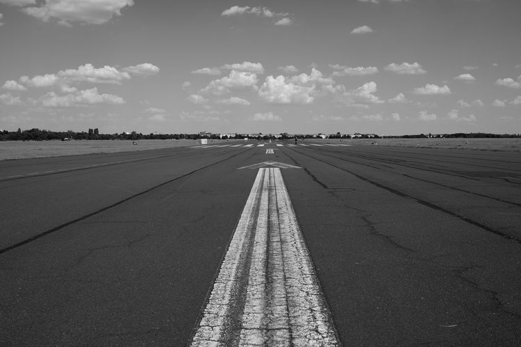 Tempelhofer Feld Blackandwhite Black & White Nikon DSLR 35mm Full Frame Berlin Photography Berlin Runway Airport Tempelhofer Feld Tempelhof Tempelhof Airport Sky Symbol Sign Transportation Direction Marking Cloud - Sky Nature Day The Way Forward Diminishing Perspective No People Sunlight Asphalt Outdoors Arrow Symbol City