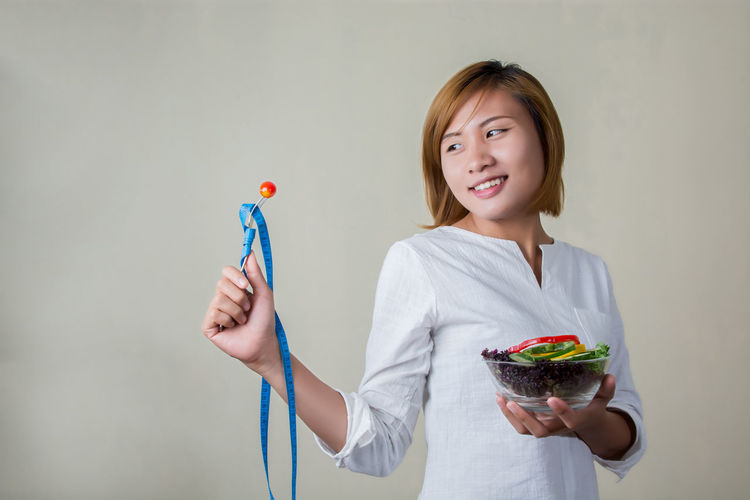 Smiling young woman holding tape measure and bowl with salad against white background