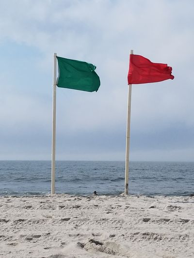 Red and green safety flags on beach against sky