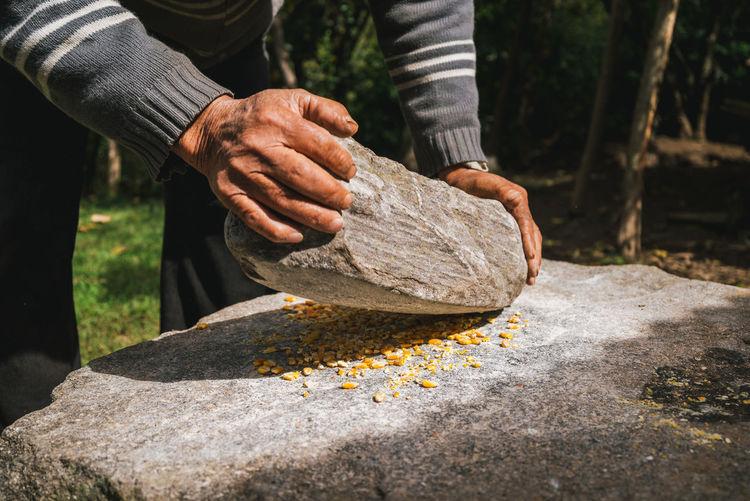 Close-up of man preparing food on millstone