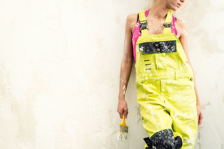 Midsection of young woman in coveralls holding paintbrush against white wall