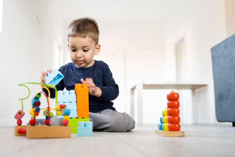 Childhood Child Toy Leisure Activity Boys Real People Indoors  Lifestyles Multi Colored Home Interior One Person Playing Casual Clothing Men Front View Cute Looking Toy Block Sitting Innocence