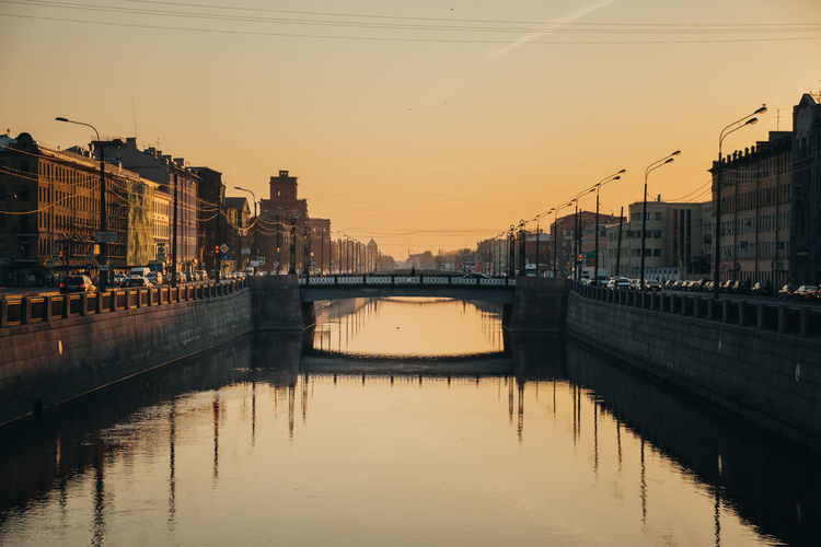 Bridge over river by buildings against sky during sunset