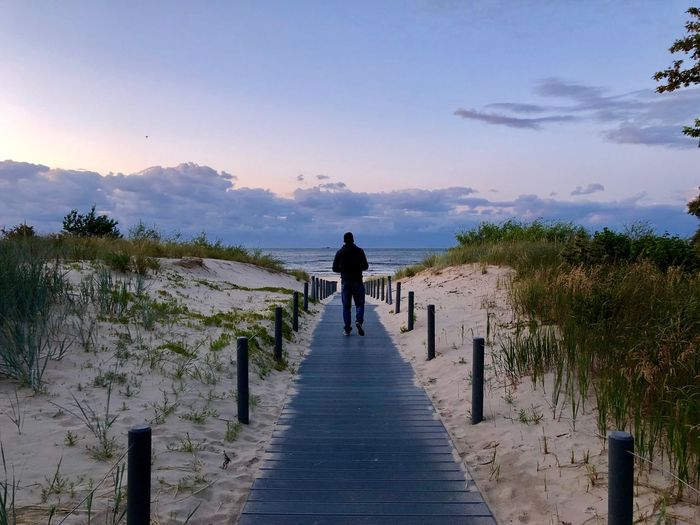 Rear view of man walking on footpath at beach against sky