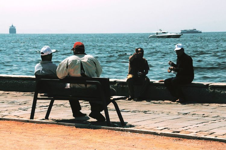 Rear view of people sitting by sea against clear sky