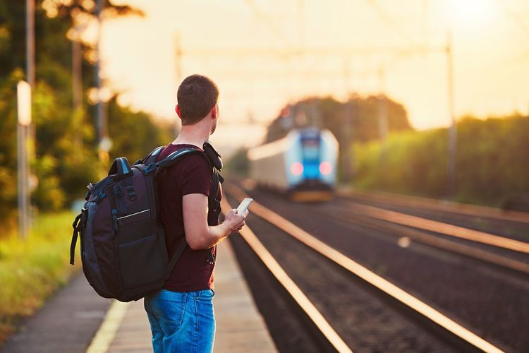 Traveler is late at the train station. Young man with backpack missed the train and waiting for next. Adventure Backpack Backpacking Journey Lifestyles Man Men One Person Outdoors People Rail Transportation Railroad Station Platform Railroad Track Railway Railway Station Real People Sunset Sunset_collection Train Train Station Transportation Travel Traveling Trip Vacations