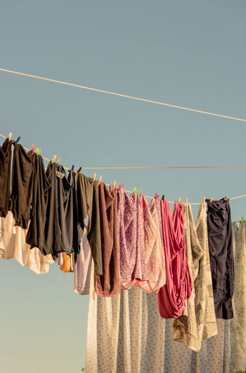 Low angle view of clothes drying on clothesline against sky
