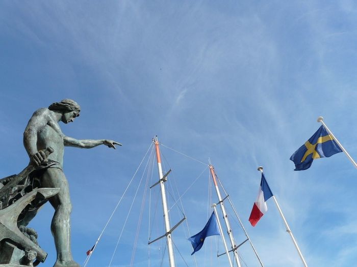 Low Angle View Of Statue Pointing Towards National Flags