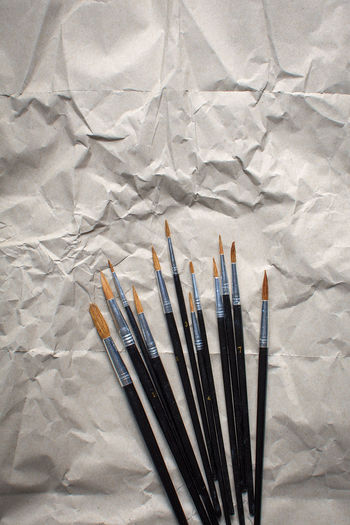 High angle view of paintbrushes on paper